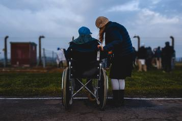a young person next to an older person in a wheelchair