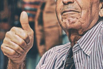 an old man with his thumbs up