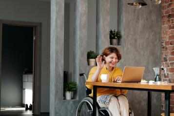 Women sitting in a wheel chair using a computer