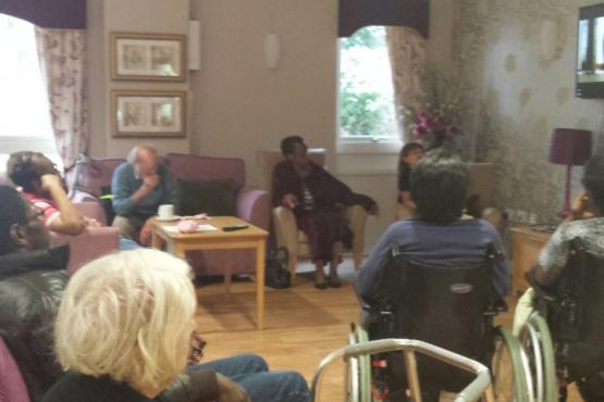 older people sitting in a care home living room