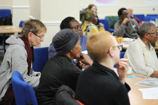 Healthwatch staff member talking to group of people