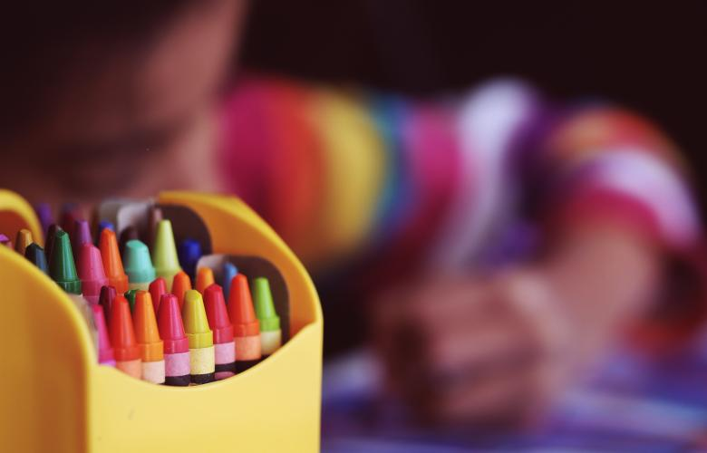 photo of a young child drawing with a box of crayons in foreground