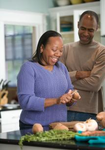 BAME man and woman cooking together