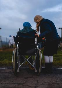 a person in a wheelchair and a person standing next to them
