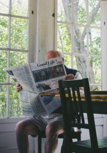 an older man reading by the window